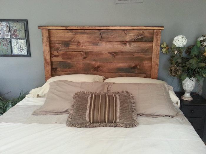 tête de lit à poser au sol en bois foncé mur gris coussins beiges et blancs couverture en blanc et gris