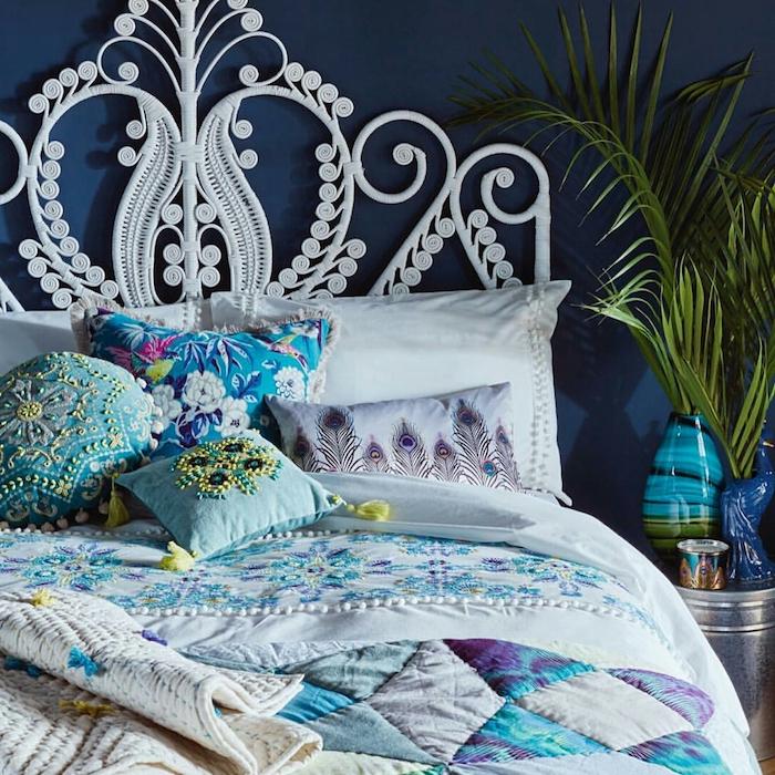 tete de lit blanche en macramé deco de coussins bleus et blancs vases bleus couverture en bleu gris violet