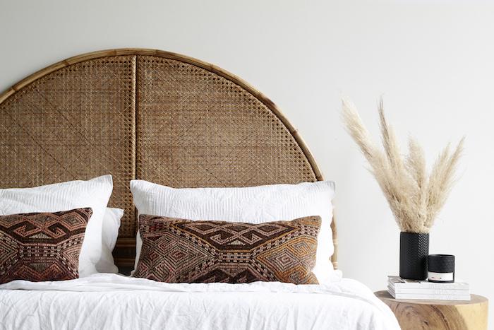 tete de lit cannage contraste avec le blanc des murs et du linge de lit deco stylée