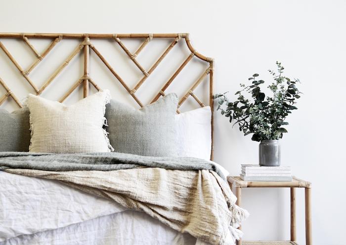 tete de lit cannage en contraste avec le mur blanc linge de lit en gris beige et blanc