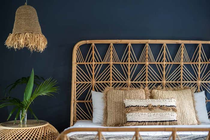 tete de lit en rotin en contraste avec mur en bleu foncé linge de lit en blanc et beige plante sur la table de nuit
