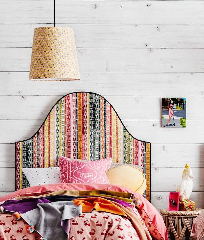 tete de lit tissu multicolore sur un mur en planches de bois blanches coussins et couvertures en couleurs différentes