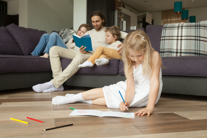 daughter playing on floor while parents and son reading book
