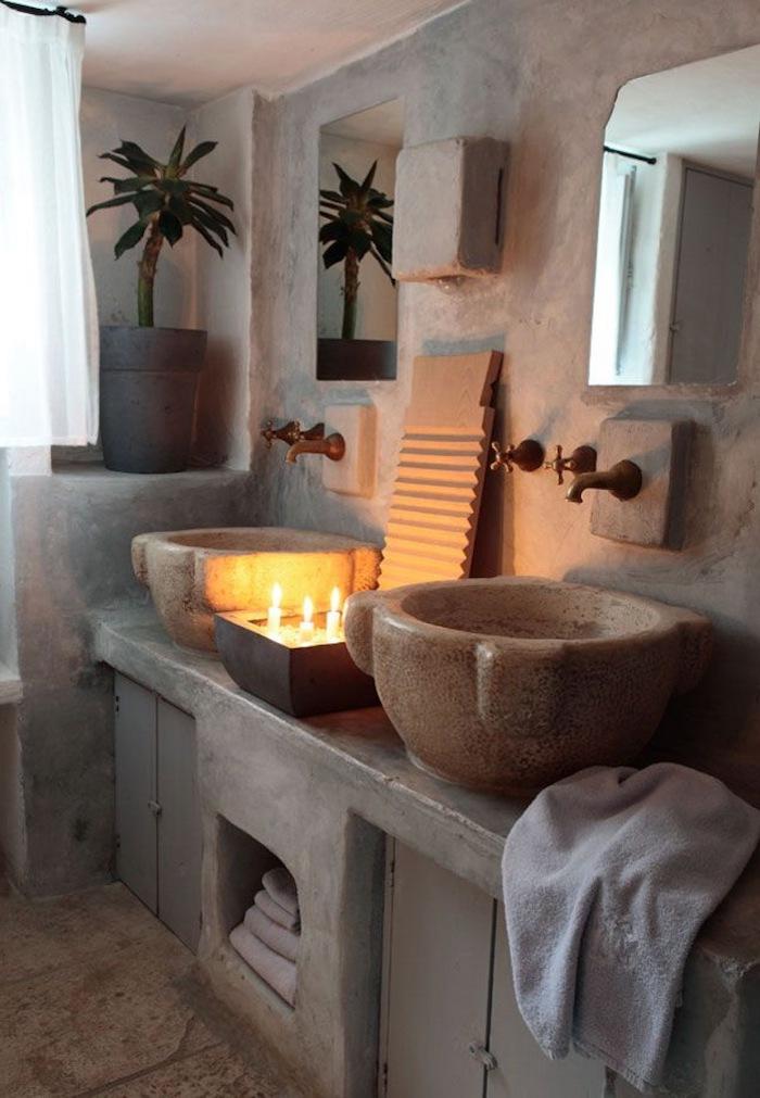 vasque en pierre meuble sous évier en pierre murs et plancher en travertin bougie et plante