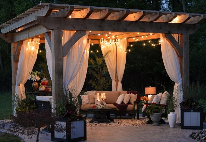 éclairage extérieur guirlande lumineuse mobilier bois rideaux blancs pergola structure bois