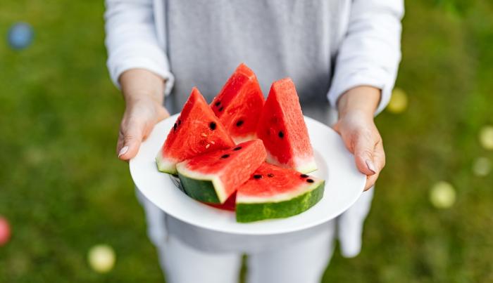 assiette ronde blanche mains femme fruits saisoniers été pasteque jardin choix fruit sucré mur