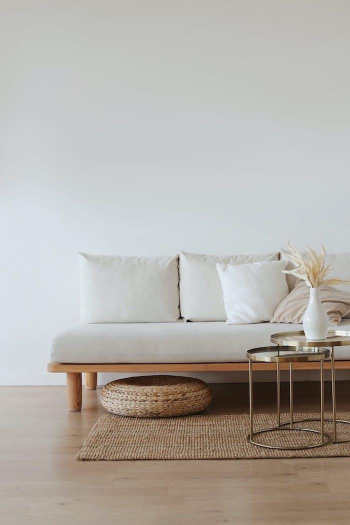 canapé de qualité en blanc et piètement boisé un bout de canapé en métal tapis beige