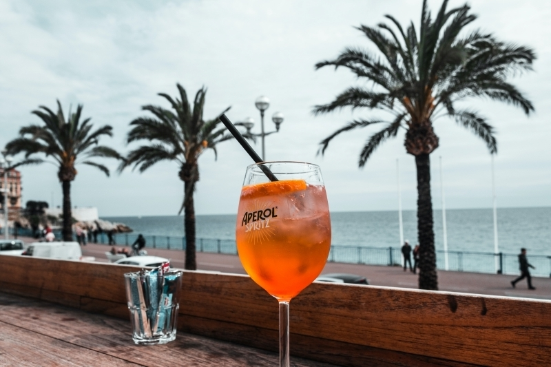 cocktail spritz préparation maison facile boisson plage été palmier terrasse bois