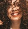 coiffure cheveux bouclés femme avec des cheveux bouclés qui sourit resized