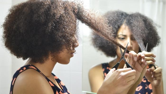 coiffure cheveux bouclés une fille qui coupe ses cheveux bouclés à sec avec des ciseaux resized
