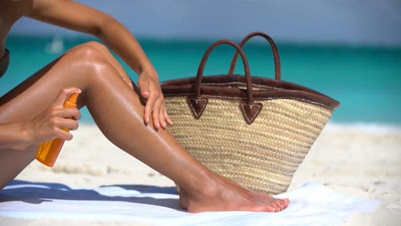 comment bronzer rapidement une femme à la plage qui applique une crème du soleil