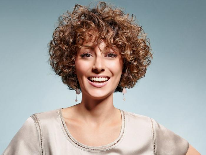 coupe très courte cheveux frisés une femme avecèune coiffure courte et frisée qui sourit resized