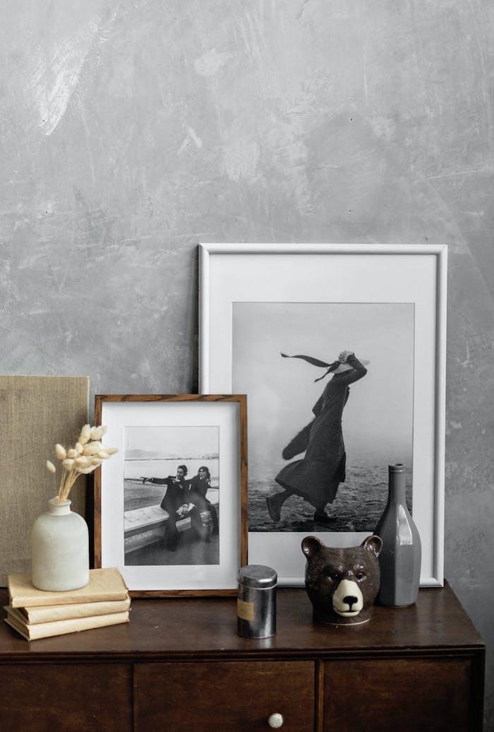 déco murale artistique de cadres de photos en blanc et en bois sur une commode en bois foncé