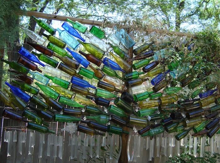 grillage avec des bouteilles de verre attachées brise vue sur mur original