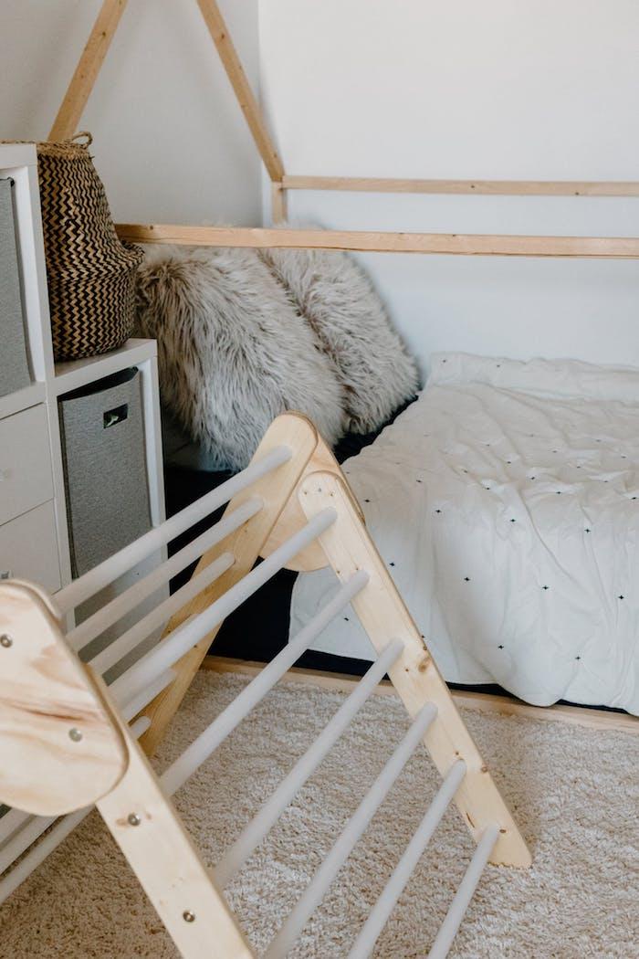 lit montessori simple avec des coussins moelleux tapis blanc toiture bois exemple lis scandinave chambre enfant