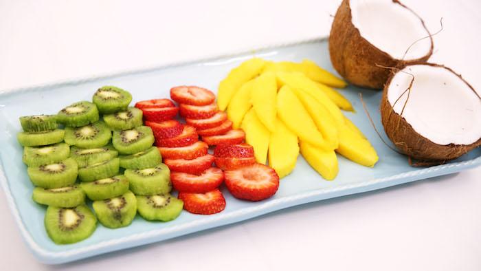 manger une mangue en salade de fruits composée de kiwi fraises noix de coco et mangue