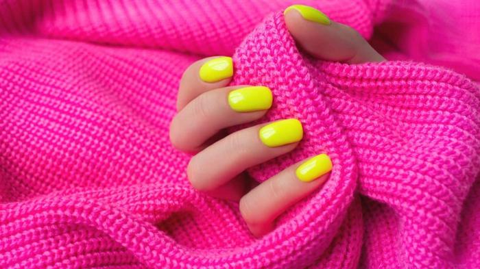 manucure été 2021 une main avec des manucures roses fluo qui tient un châle