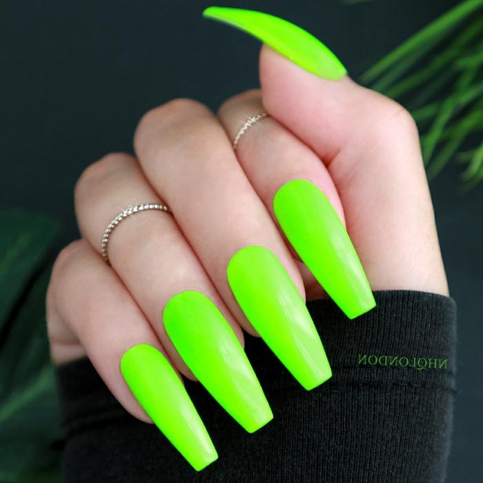 ongle vert la paume qui tient un flocon de vernis vert fluo
