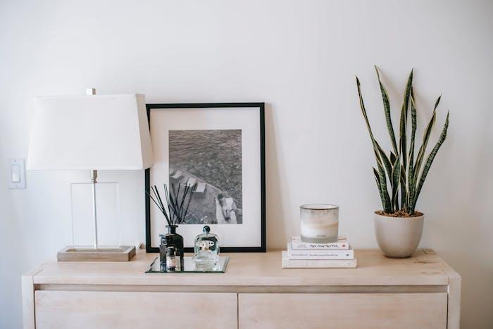 photo en noir et blanc avec cadre noir sur une commode en bois clair contraste avec le mur blanc