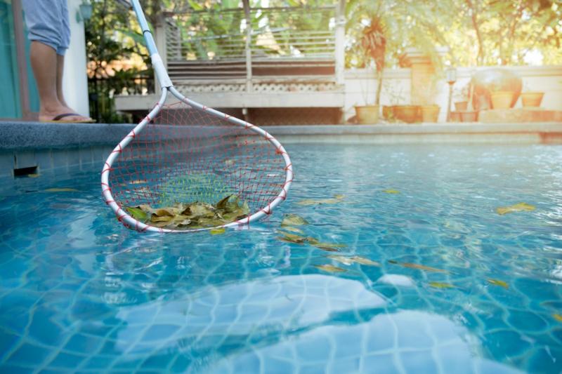 piscine extérieure un homme qui ramasse les feuilles tombées dans la piscine