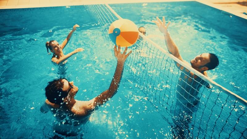 plante autour piscine des gens qui jouent au volleyball aquatique
