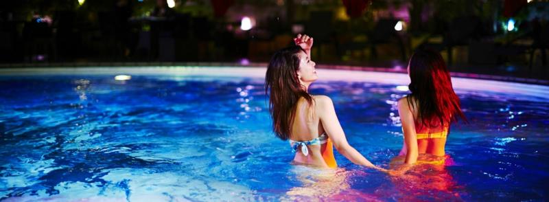 plante bord de piscine deux amies dans la piscine pour un bain nocturne