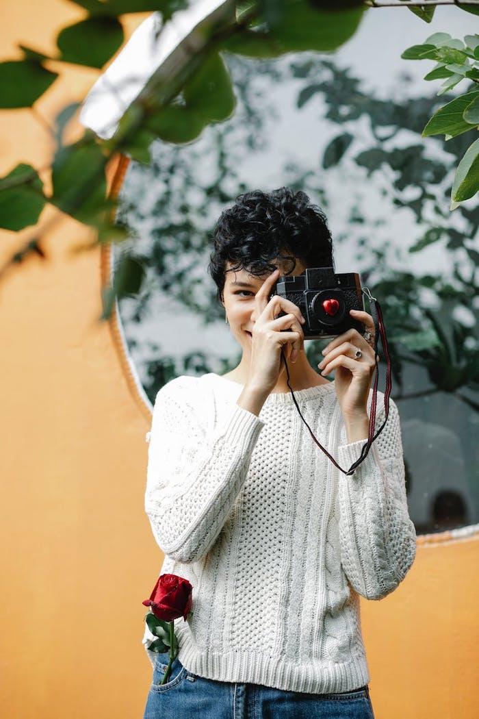 prise de photo par une fille souriante au cheveux courts bouclés rose dans la poche
