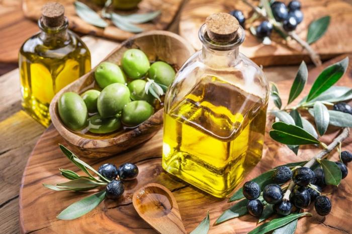 régime méditerranéen huile d'olive dans une bouteille à côté d'une branchette d'olive