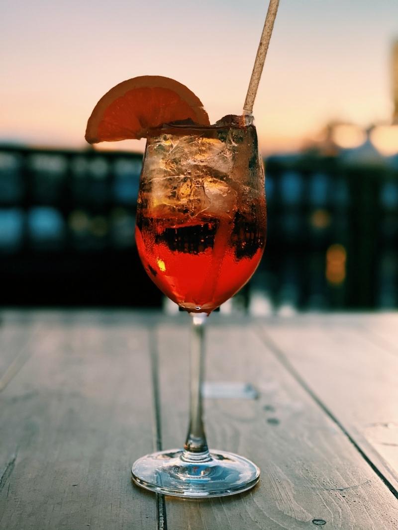 recette spritz verre aperol spritz tranche de citron coucher de soleil été table bois