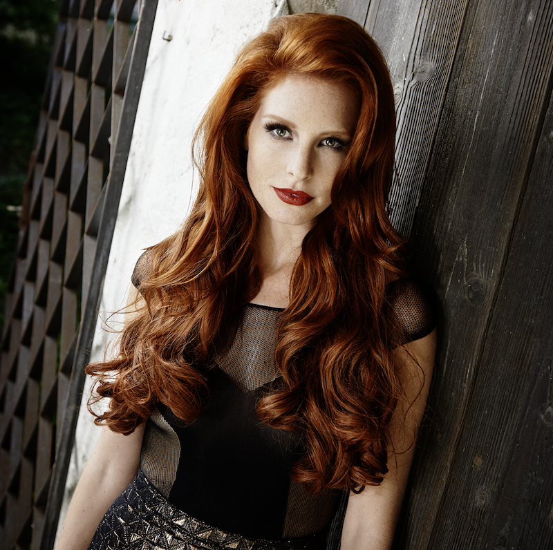 cheveux roux femme au teint clair en tenue noire et lèvres rouges