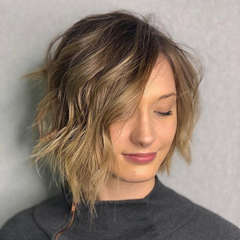 coupe asymétrique coiffure boucles méches blond miel cheveux chatain