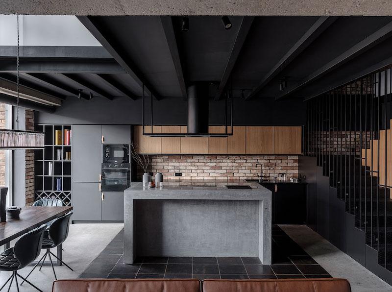 cuisine noir et bois avec ilot central en gris plafond et escalier en noir