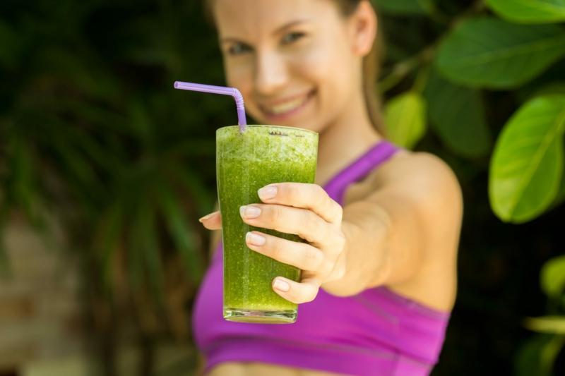 cure detox foie une femme qui propose un smoothie vert