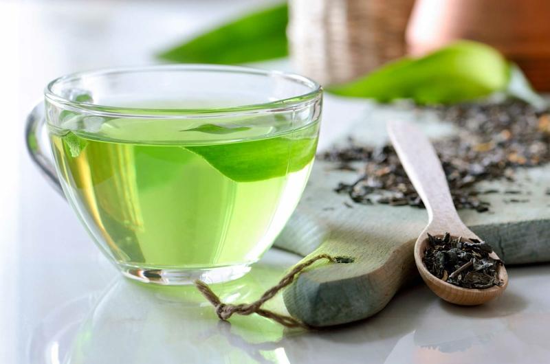 détoxifier le foie une verre de thé vert et une planche de bois