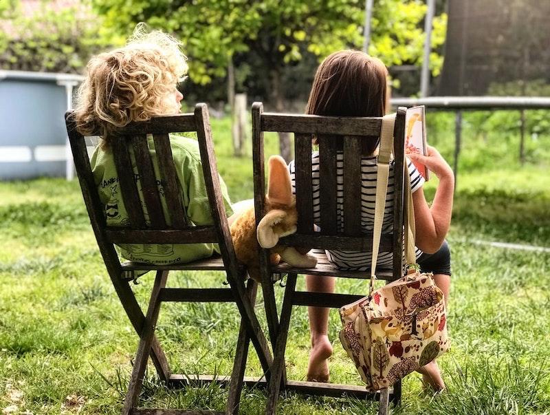 deux enfants assis sur deux chaises dans le jardin