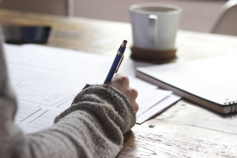 femme au pull beige qui dessine sur papier blanche
