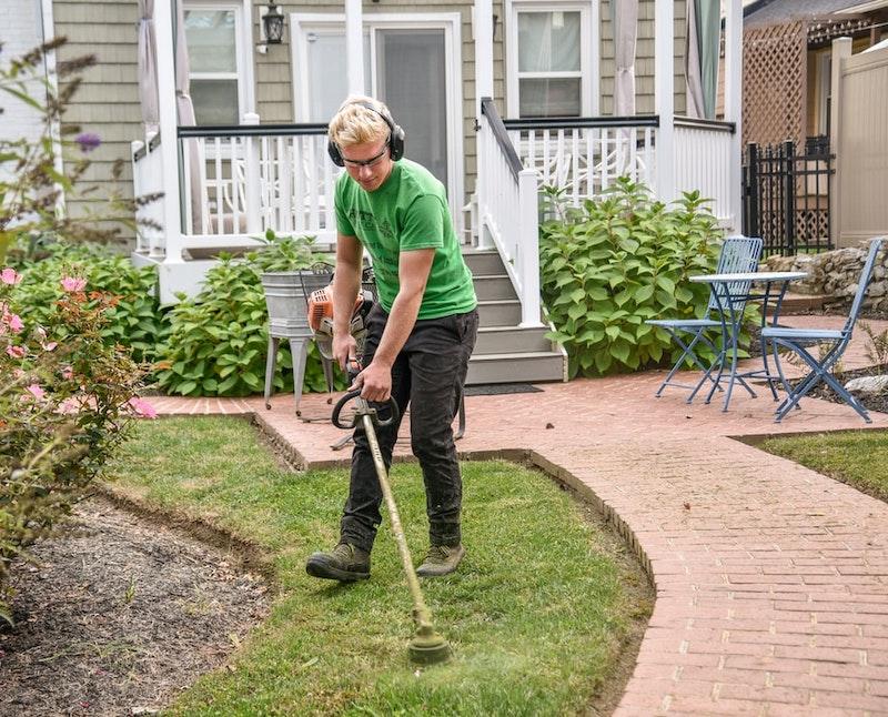 homme qui tond la pelouse verte devant une maison