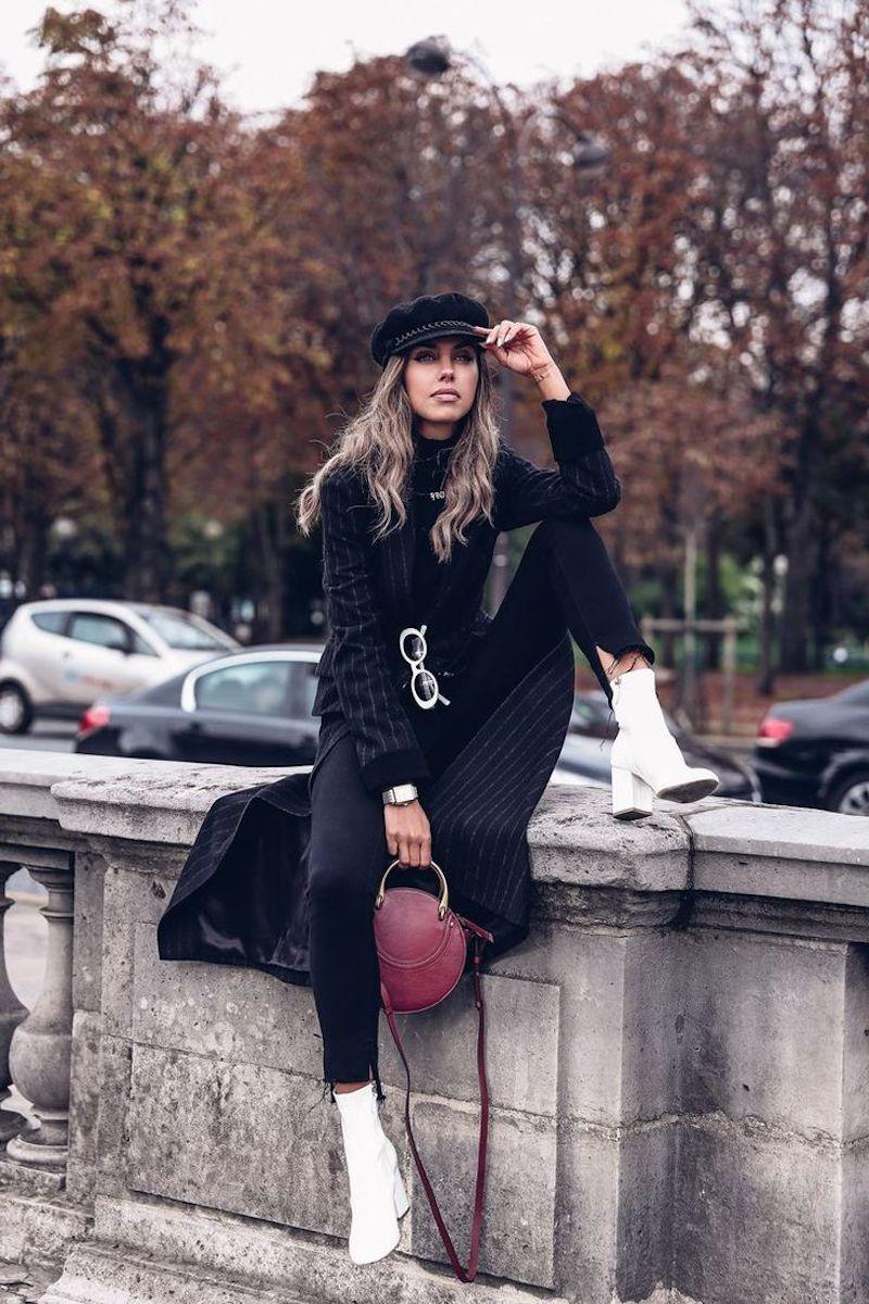 look chic femme en tenue noire avec bottines blanches sac à main en bordeaux