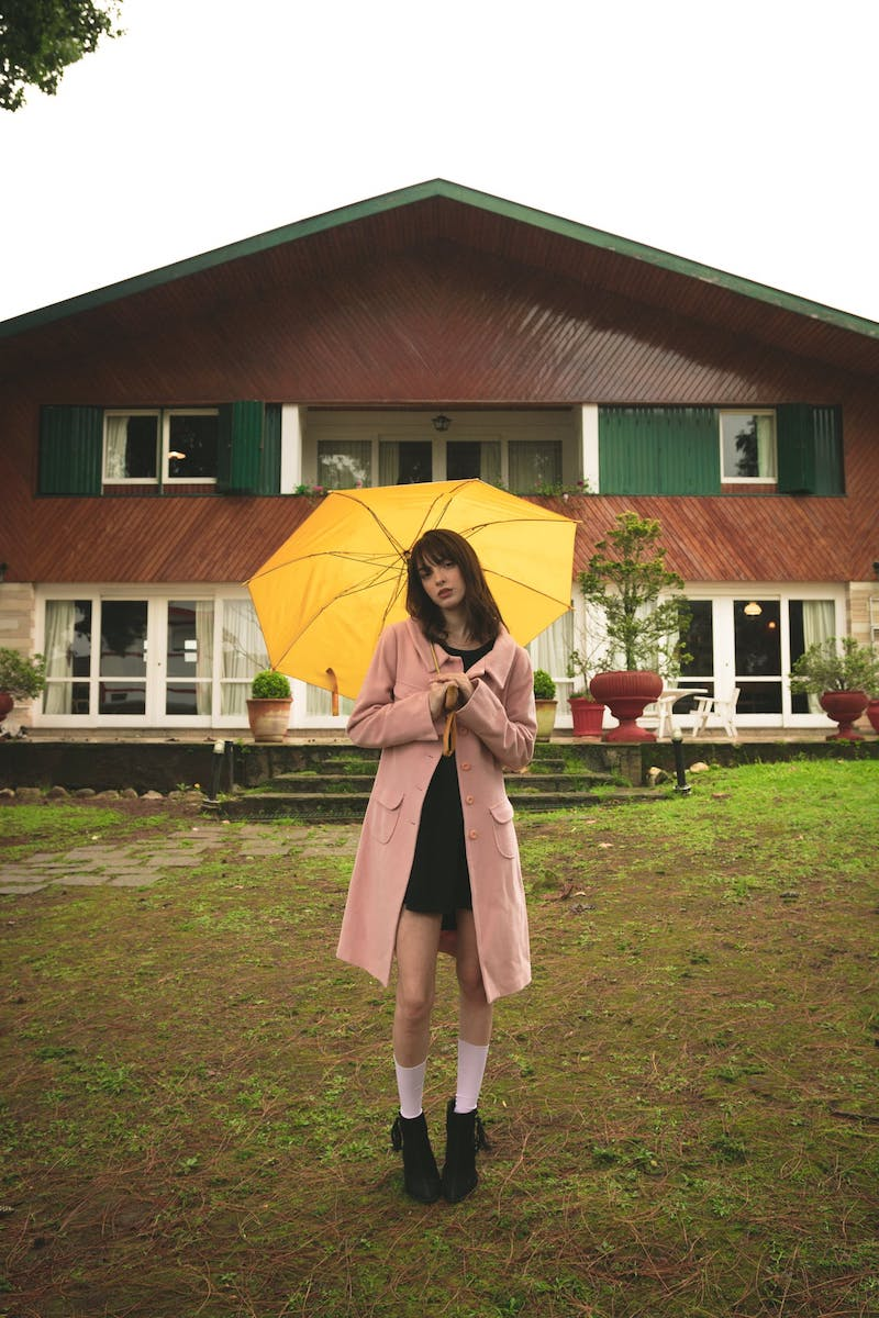 parapluie d une couleur jaune contrastant manteau rose femme stylée tenue de pluie