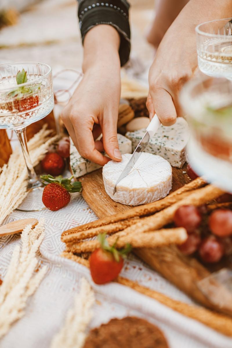 presentation planche charcuterie fromage une femme qui tranche du fromage