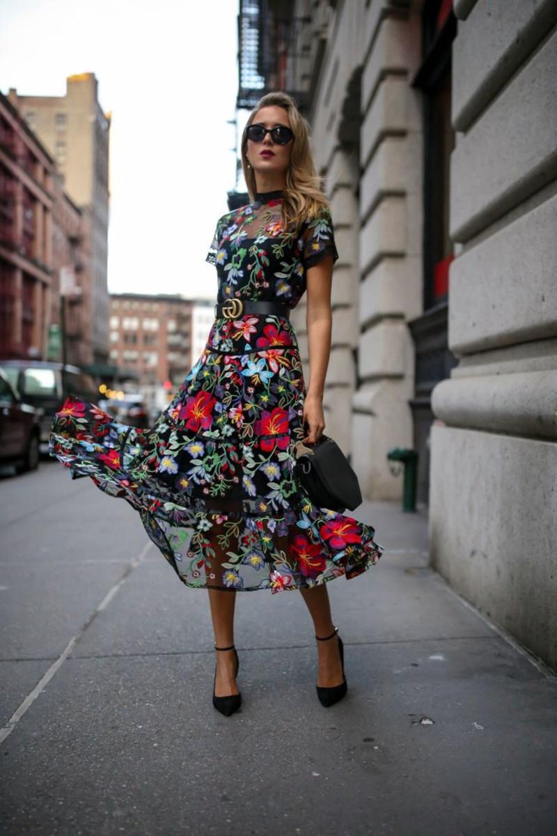 robe femme habillée fond noir fleurie femme aux escarpins et sac a main noirs