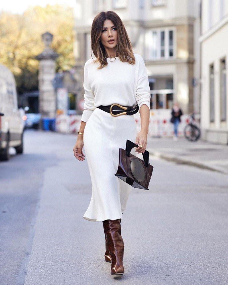 robe longue hiver blanche ceinturée femme aux bottes marron et sac à main en cuir