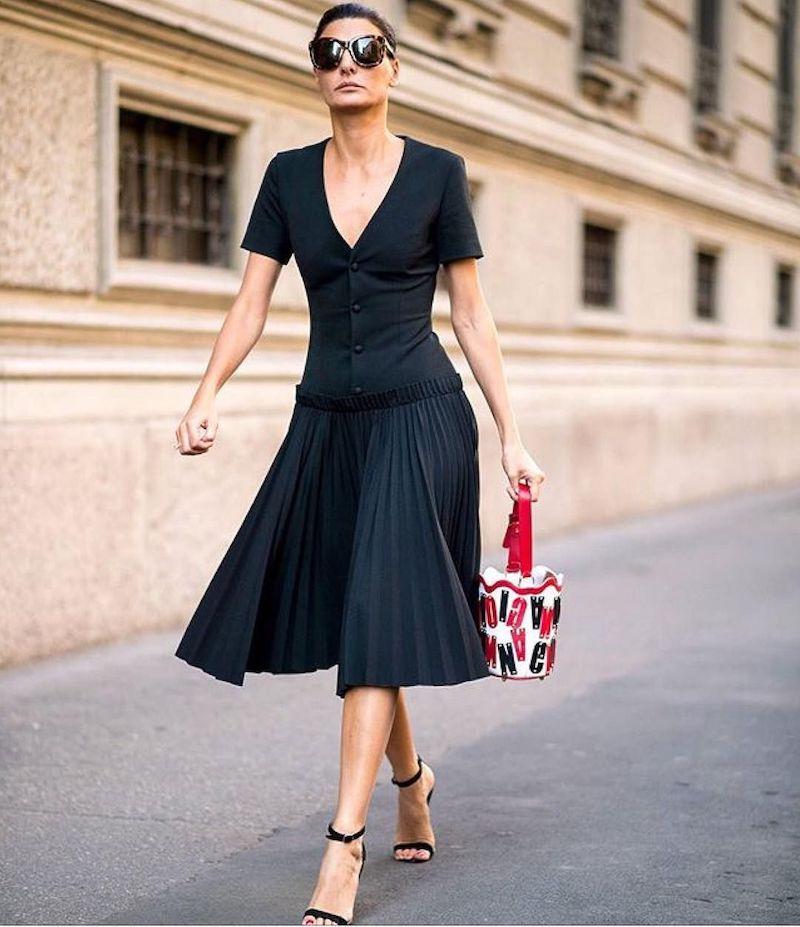 style classe femme en robe noire sandales et lunettes de soleil