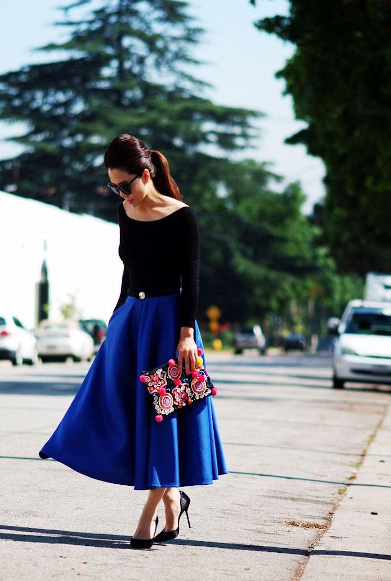 style romantique jupe midi en bleu top et chaussures noirs pochette comme accent