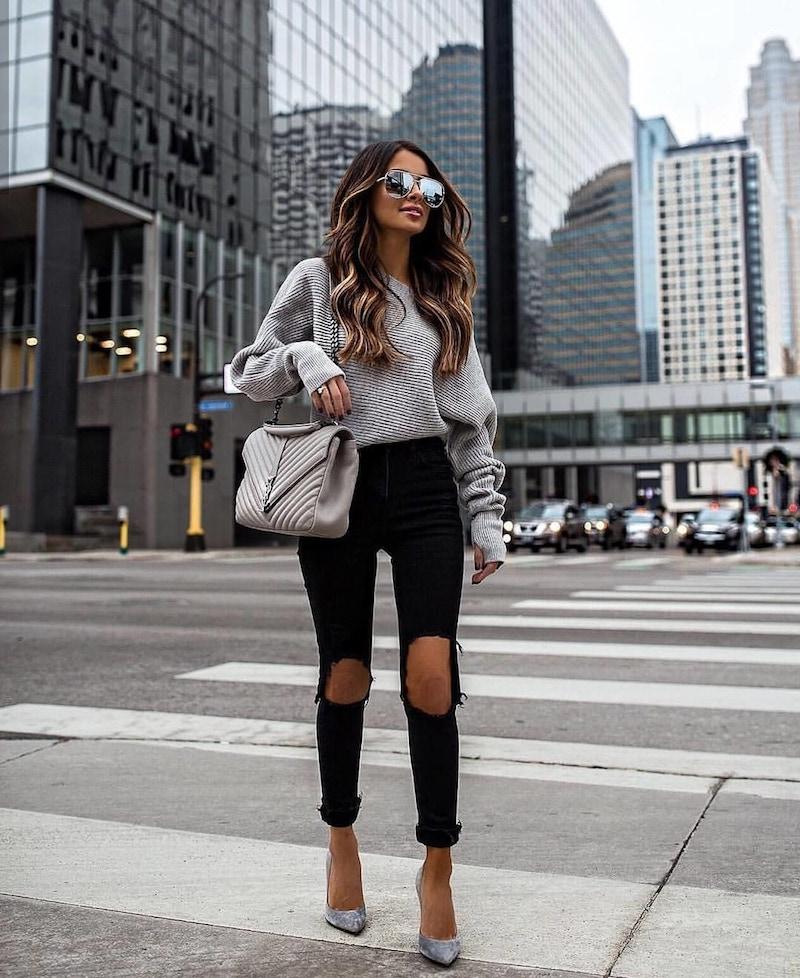 tendance automne hiver 2021 2022 femme en jeans noirs déchirés et pull over
