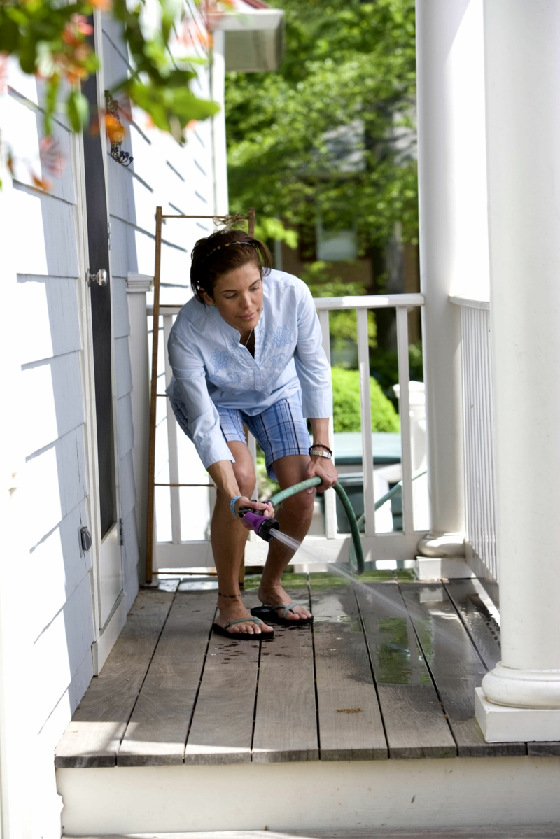 younger women use the water hose to wash her patio