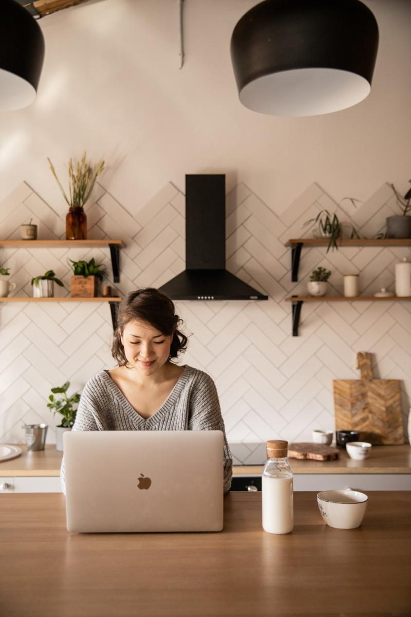 amande vitamine une femme qui travaille sur son ordinateur et boit du lait