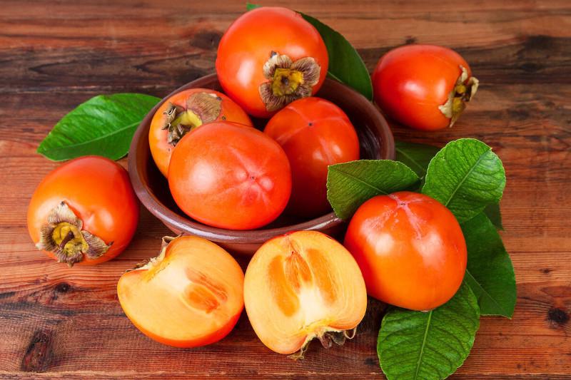 bienfaits du kaki pour le visage fruit coupé en deux sans noyau feuille et peau qui peuvent être consommées