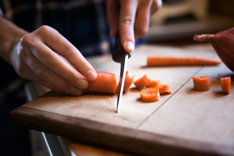 blanchir carotte un couteau qui coupe une carotte sur une planche de bois