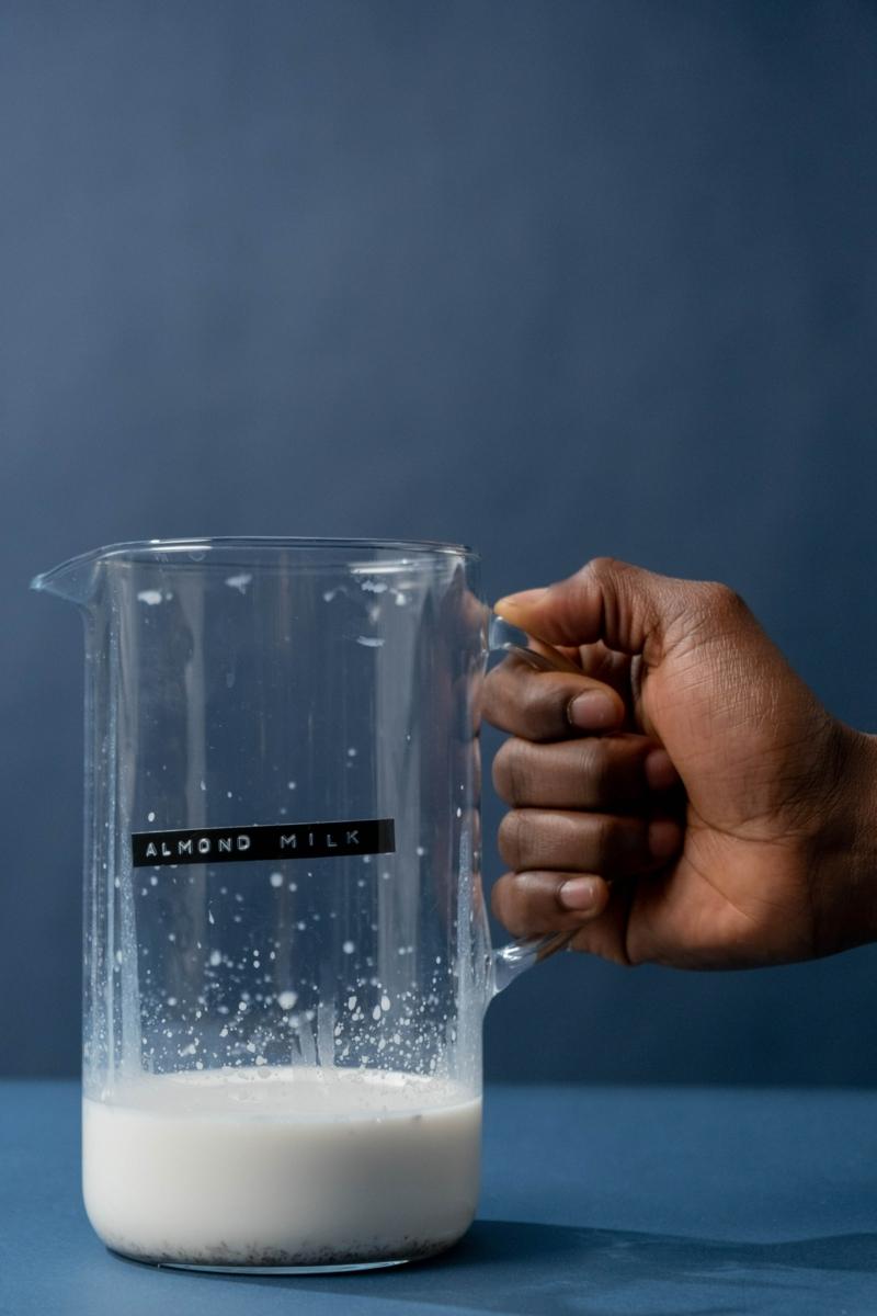calorie lait une main qui tient un broc de lait d amande